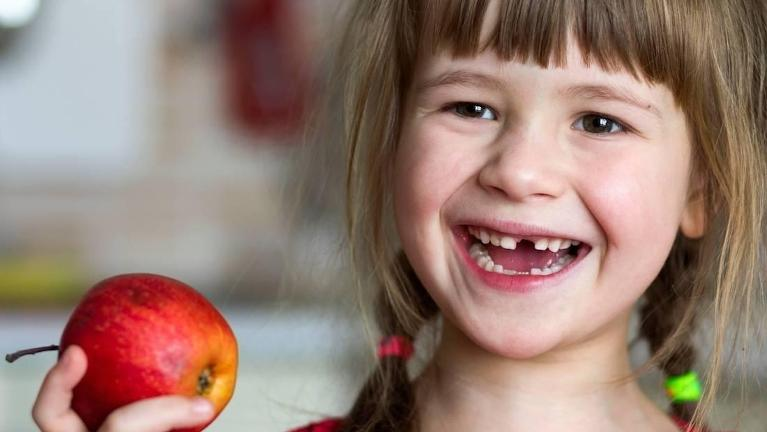 young girl eating red apple l kid's dentist allentown