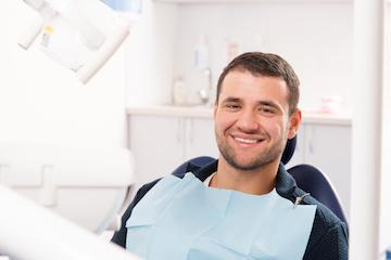 man smiling in dental exam chair l tooth extraction allentown